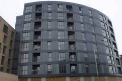 Okna drewniano – aluminiowe, kolor antracyt, widok na front budynku wielopiętrowego, okna balkonowe, duże przeszklenia. Bryła budynku zaokrąglona