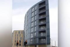 Okna drewniano – aluminiowe, kolor antracyt, widok bokiem na budynek wielopiętrowy, okna balkonowe, duże przeszklenia