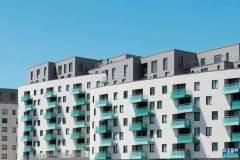 Okna drewniano – aluminiowe, kolor antracyt, widok od zewnątrz, kolor elewacji biały, balkony turkusowe, błękitne niebo.