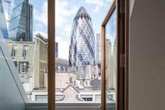 Okna drewniano – aluminiowe, kolor naturalny dąb, widok przez otwarte okno na apartamentowce, okno balkonowe
