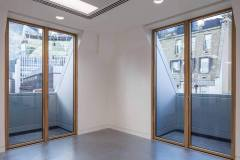 Okna drewniano – aluminiowe, kolor naturalny dąb, widok od wewnątrz na okna balkonowe w narożniku.