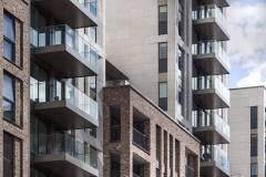 Okna drewniano – aluminiowe, okna balkonowe, kolor antracyt, widok od zewnątrz na budynek apartamentowca, elewacja z cegły i płyt piaskowca, przeszklone balkony.