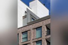 Okna drewniano – aluminiowe, okna balkonowe, kolor antracyt, widok od zewnątrz na budynek apartamentowca, elewacja z cegły i płyt piaskowca.