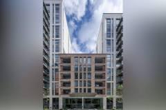 Okna drewniano – aluminiowe, okna balkonowe, kolor antracyt, widok od zewnątrz na cały budynek apartamentowca od strony wejścia, elewacja z cegły i płyt piaskowca.