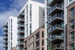 Okna drewniano – aluminiowe, okna balkonowe, kolor antracyt, widok od zewnątrz na budynek apartamentowca, elewacja z cegły i płyt piaskowca, przeszklone balkony i tarasy.