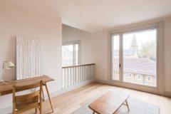 Okna drewniano – aluminiowe, kolor biały, widok na okno balkonowe z wnętrza pokoju. Na części otwieranej okna balkonowego balustrada