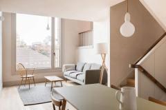 Okna drewniano – aluminiowe, kolor biały, widok przez wnętrze apartamentu na okno balkonowe. Na części otwieranej okna balkonowego balustrada.