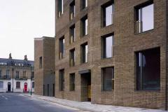 Okna drewniano – aluminiowe, kolor antracyt, widok z ulicy na front budynku. Elewacja budynku z cegły.