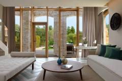 Okna drewniano – aluminiowe, kolor naturalny dąb. Widok z wewnątrz obszernego apartamentu na wyjście na taras i ogród. Ściana w postaci przeszklenia z przeszklonymi drzwiami i dużym oknem przesuwnym.