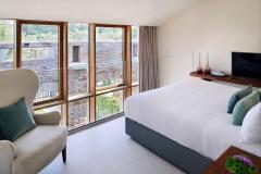 Okna drewniano – aluminiowe, kolor naturalny dąb. Widok od środka z pokoju hotelowego. Zewnętrzna ściana cała przeszklona, podzielona na części otwierane i fixy.