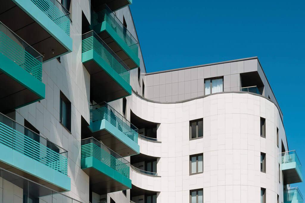 Okna drewniano – aluminiowe, kolor antracyt, widok od zewnątrz, bryła budynku pofalowana, kolor elewacji biały, balkony turkusowe