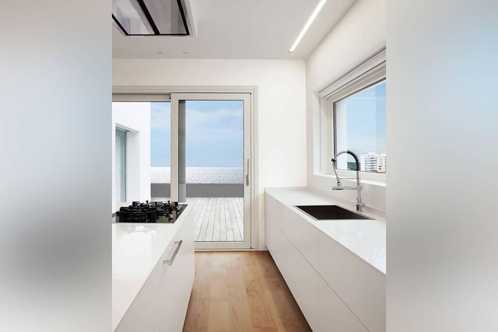 Okna drewniano – aluminiowe, kolor biały SILK, widok od środka apartamentu przez kuchnie z widokiem na morze