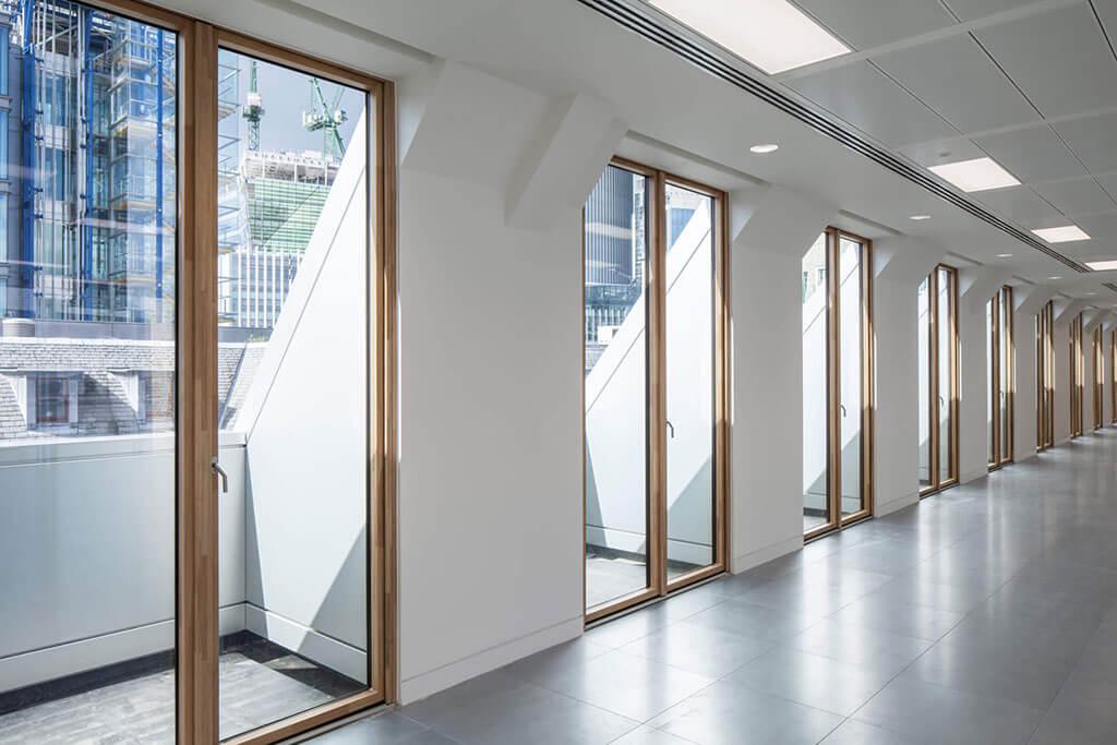 Okna drewniano – aluminiowe, kolor naturalny dąb, widok na rząd okien balkonowych z otwartej przestrzeni.