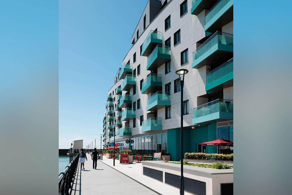 Okna drewniano – aluminiowe, kolor antracyt, widok od zewnątrz z nadmorskiego bulwaru, kolor elewacji biały, turkusowe balkony.