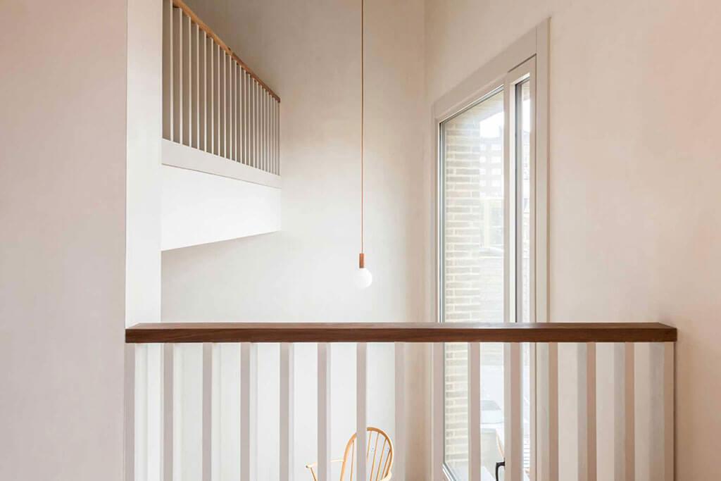 Okna drewniano – aluminiowe, kolor biały, widok z wnętrza apartamentu, z antresoli na okno balkonowe.