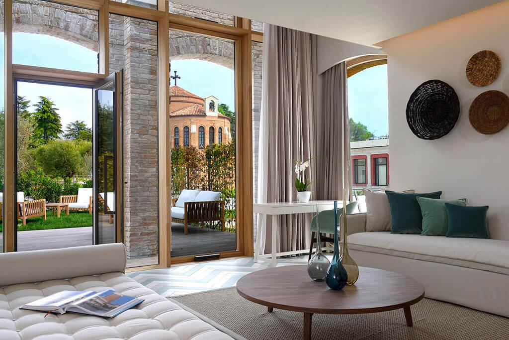 Okna drewniano – aluminiowe, kolor naturalny dąb. Widok z wnętrza apartamentu na wyjście na taras i ogród. Ściana przeszklona podzielona na części stałe i otwierane.