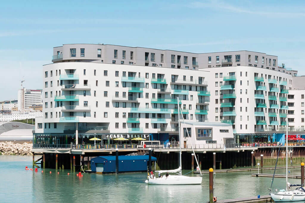 Okna drewniano – aluminiowe, kolor antracyt, widok z morza od zewnątrz na całą bryłę apartamentowca, kolor elewacji biały, balkony turkusowe.