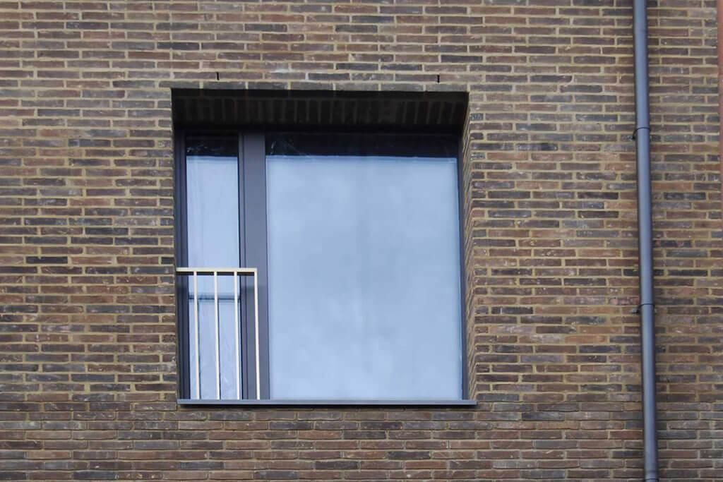 Okna drewniano – aluminiowe, kolor antracyt, widok z zewnątrz na pojedyncze okno balkonowe, duża fixa i wąska cześć otwierana z widoczną balustradą.